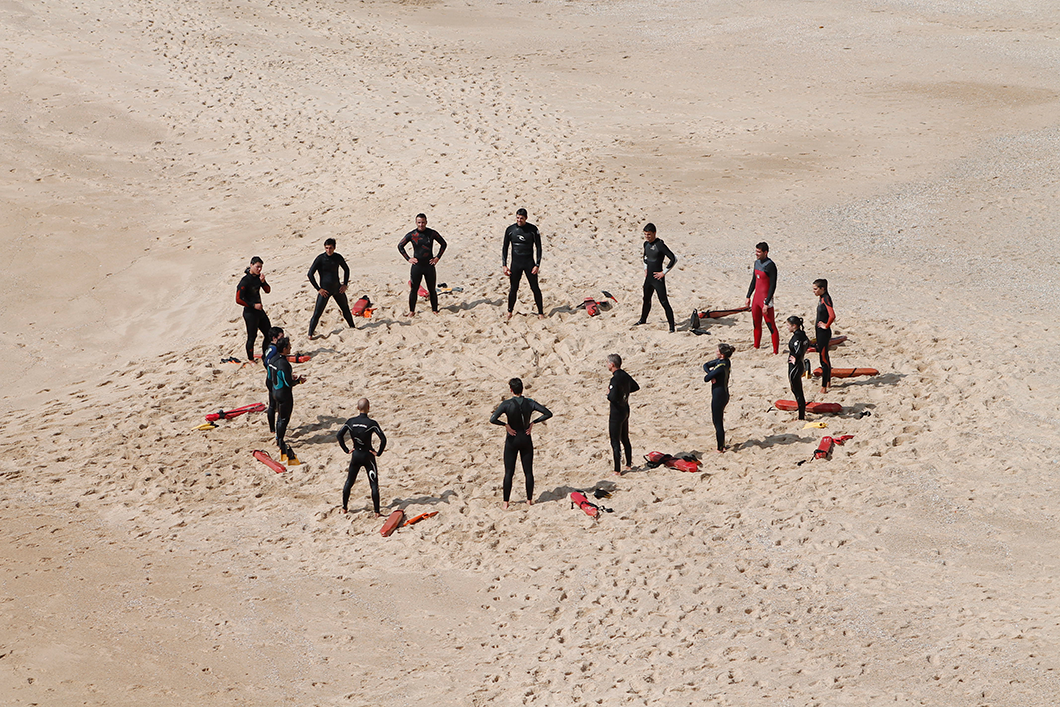 group of people standing in a circle on beach