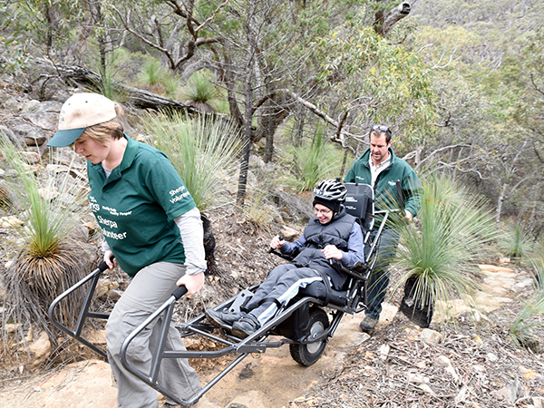 2 adults assisting child in wheelchair up a steep rocky bush path