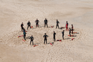 group of wet-suited people standing around in a circle on a beach