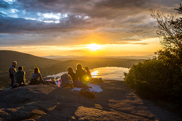 A group of people sitting together on a mountain overlooking a valley whilst the sun sets
