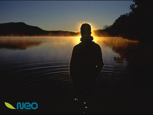 silhouette of person standing in front of lake at sunrise