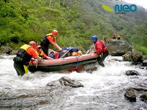 bunch of people whit water rafting stuck on rocks