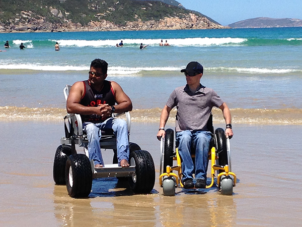 Two guys in beach wheelchairs on the beach