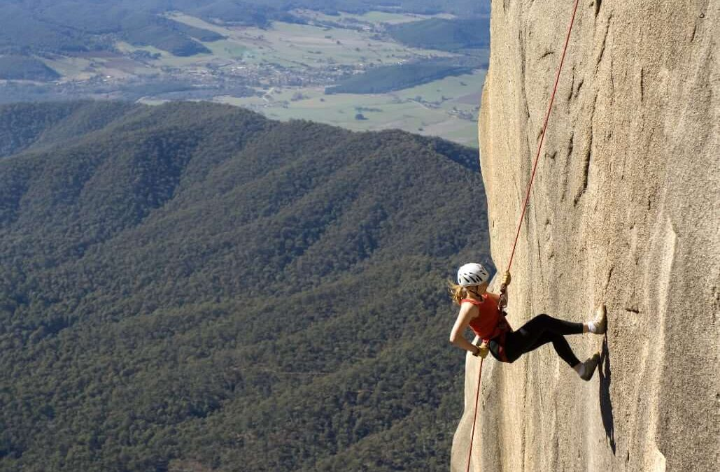 person climbing on rock face