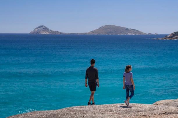 2 people walking on a beach
