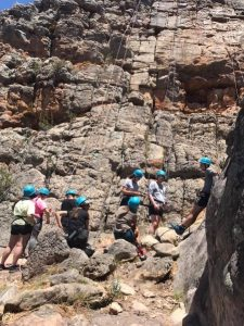 a bunch of people with blue safety hats and harnesses on standing against rocks
